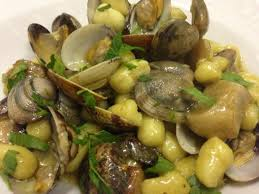 Piatto con chicche di ricotta agrumate con vongole , pinoli e stridoli